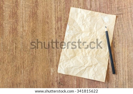 old paper with black pencil on wooden table - stock photo