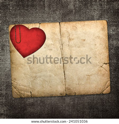 old paperboard card with red paper heart on a dark fabric background  - stock photo