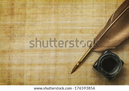 Old  Papyrus Paper and Feather Quill with Glass Ink Bottle and Copy Space. - stock photo