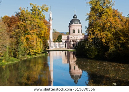 Old park Schwetzingen, Germany - mosque with minaret reflected in  water of  pond, autumn colorful landscape on  sunny day