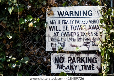 Old parking warning sign between vegetation on wall - stock photo