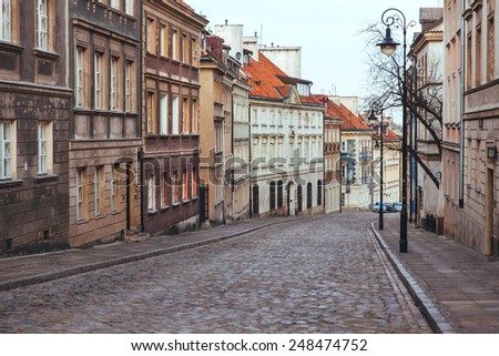Old, paved road in the old town with old tenement houses around - stock photo