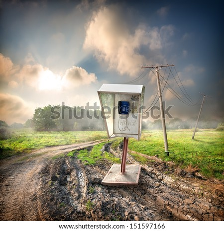 Old payphone on a road in the field - stock photo