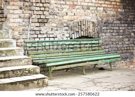 Old peeling paint green bench next to brick wall. - stock photo