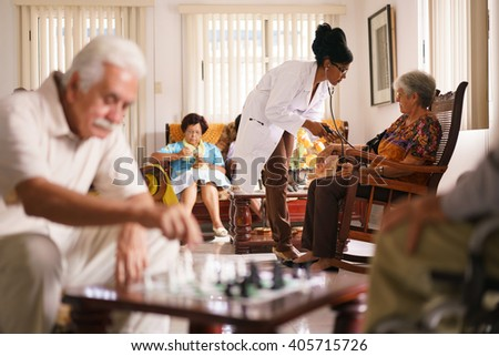 Old people in geriatric hospice: Black doctor visiting an aged patient, measuring blood pressure of a senior woman. Group of retired men in foreground playing chess. - stock photo
