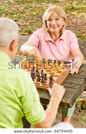 Old people playing chess in the park.