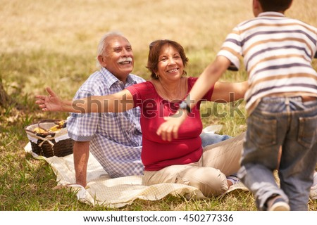 Old people, senior couple, elderly man and woman. Outdoor family having fun with happy grandpa and grandma hugging boy at picnic in park. - stock photo