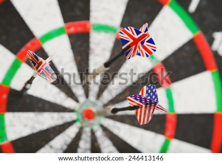 old perforation dartboard with flags on darts. focus on flag - stock photo