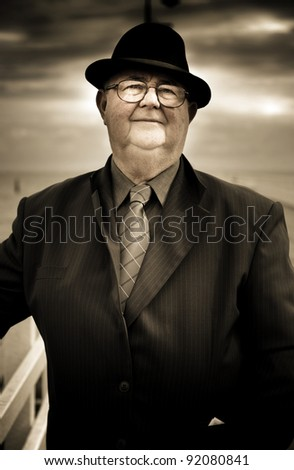 Old Person Standing By A Railing At A Beach Location Wearing Business Suit And Tie Thinking, Recalling And Recollecting Years When Reminiscing About Bygone Days - stock photo