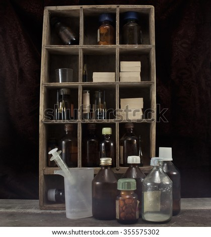 Old pharmacy alchemist table. Old pharmacy medicine alchemy table with bottles on shelves and dirty syringe. - stock photo