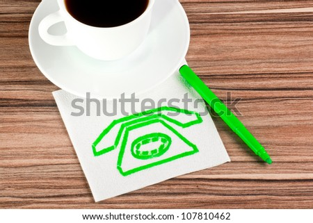 Old phone on a napkin and cup of coffee - stock photo