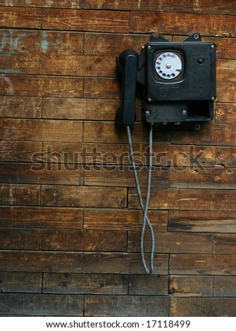 Old phone on a wooden wall - stock photo