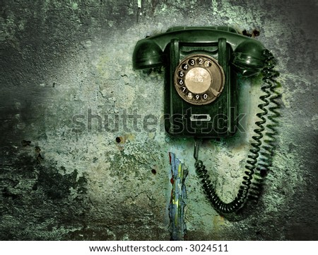 Old phone  on the destroyed wall - stock photo