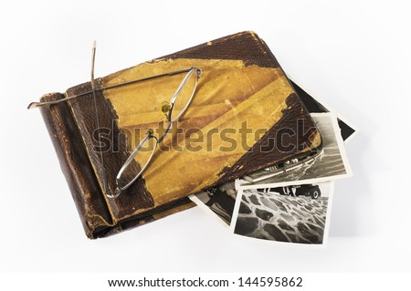 Old photo album. An old photo album with a pair of glasses on it in white background - stock photo