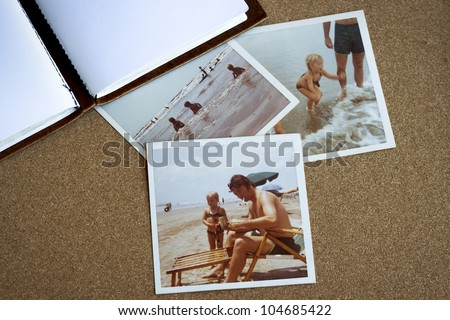 Old photo album and photographs from the early 1970's of family at a beach on a bulletin board. - stock photo