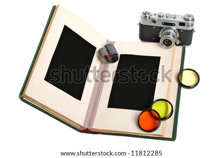 Old photo album with empty pictures and vintage camera with photofilters - stock photo