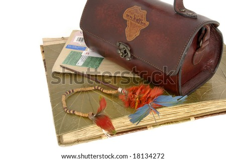 Old photo album with ethnic feathers and purse isolated against a white background