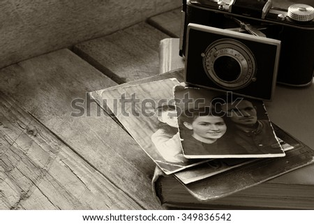old photo camera, antique photos and old book on wooden table. black and white style image. selective focus  - stock photo