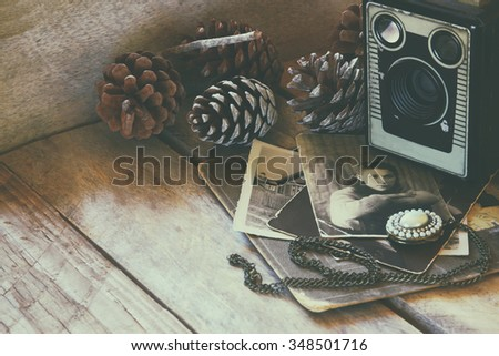 old photo camera, antique photos on wooden table. faded style retro filtered image. selective focus - stock photo