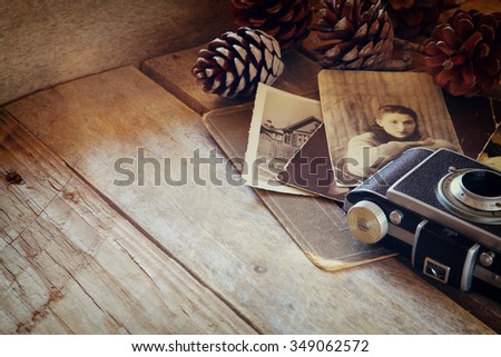 old photo camera, antique photos on wooden table. retro filtered image. selective focus - stock photo