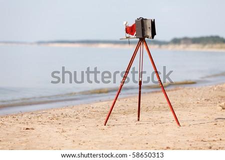 Old photo camera on tripod setup in beach - stock photo