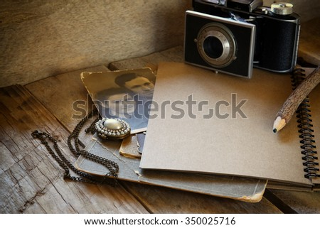 old photo camera, open notebook and antique photos on wooden table. retro filtered image  - stock photo