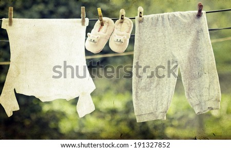 Old photo of baby clothes hanging on the clothesline. - stock photo