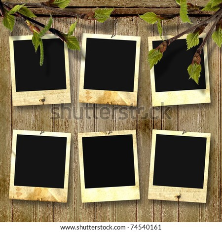Old photoframes are hanging on the vintage wooden background. - stock photo