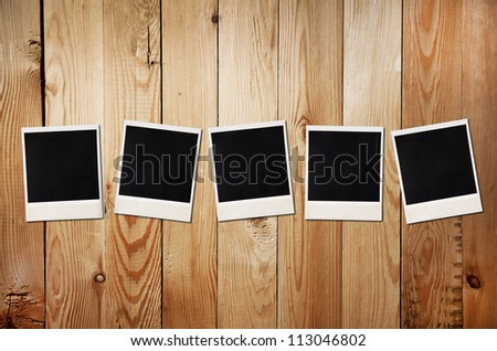 Old photos on a wooden background, free space for 5-letter word or photo - stock photo