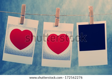 old photos with the image of heart valentine hanging on a rope on clothespins - stock photo
