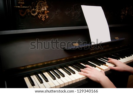 Old piano with players hands - stock photo