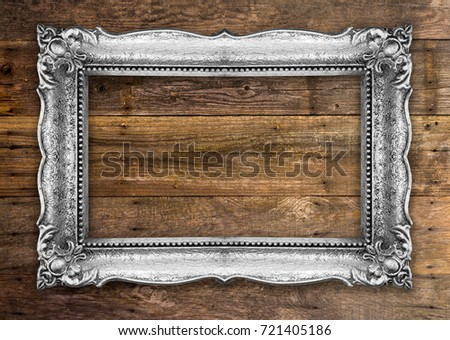 Old Picture Frame on wooden baclground wall, silver metal