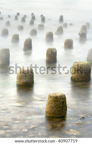 Old pier in the fog - stock photo