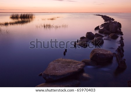 Old pier protecting shores of the Baltic Sea on a long exposure shot early in the morning. - stock photo