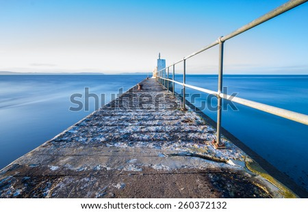 Old pier with metal railing and small lighthouse. (Nairn harbour, Scotland.) - stock photo