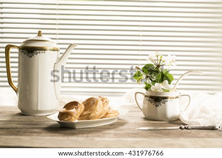 old pitcher, a glass, a roll, and apple flowers on a wooden table - stock photo