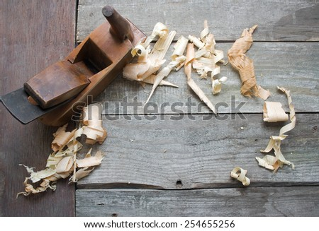 Old plane hand tool. Old rusty and dirty carpenter`s wooden hand tool lying on a wooden table with sawdust background. - stock photo