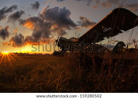 old plane on a sunset background - stock photo