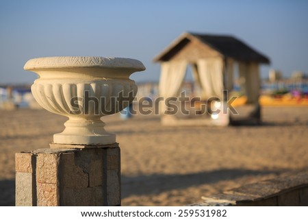 Old plaster vase in antique style on a background of a sandy beach and a canopy. Shallow depth of field. - stock photo