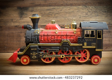 Old plastic toy train on wooden background with many dust on a train.