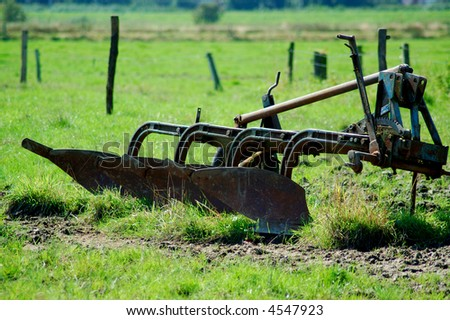 Old plow on a meadow