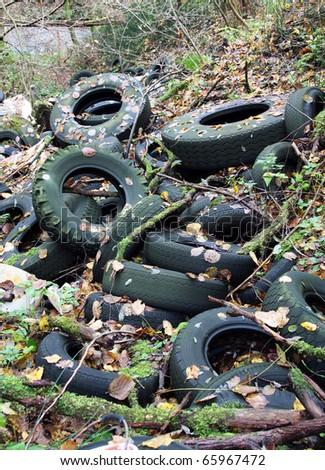 Old pneumatics in illegal dump - stock photo