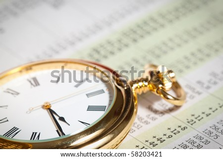 Old pocket watch close up on stock market numbers - stock photo