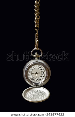 Old pocket watch hanging on a chain. Dark background. - stock photo