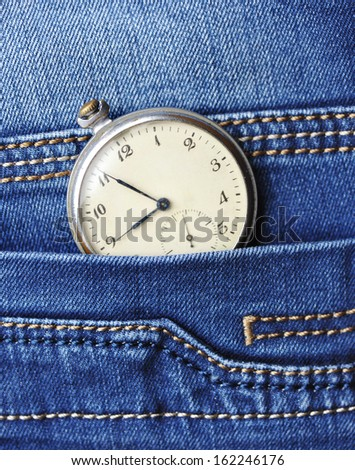 Old pocket watch in the pocket of blue jeans - stock photo