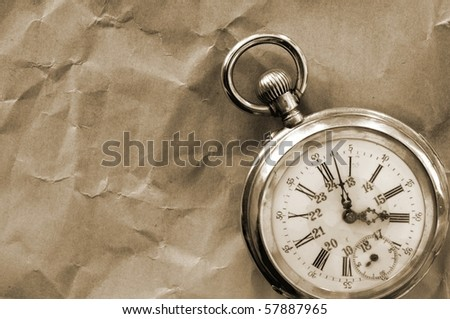 old pocket watch isolated on crinkly paper - stock photo