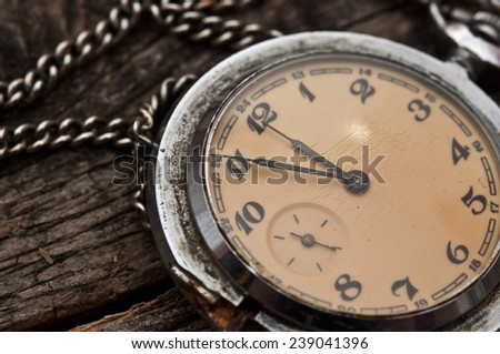 Old pocket watch on a rustic vintage wooden background - stock photo