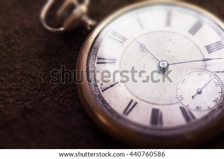 Old pocket watch on grungy leather surface. Shot in low key and extremely shallow depth for impressional feel. Focus is on etching of clock face plate. - stock photo