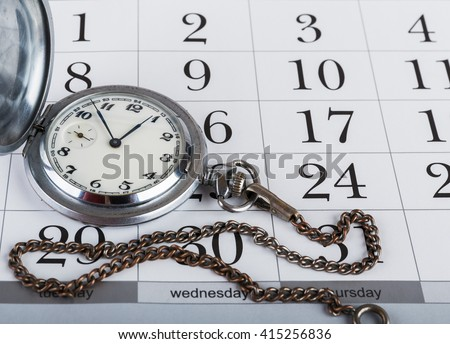 Old pocket watch on the calendar - stock photo