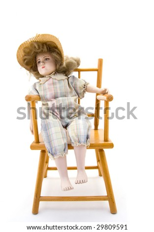 Old porcelain doll in a wooden chair on white